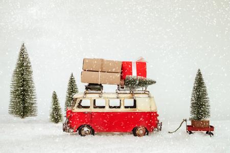 Fondo de postal Vintage Feliz Navidad - coche antiguo en miniatura con regalos (caja de regalo) en el techo y el árbol de Navidad en el bosque de invierno cubierto de nieve.