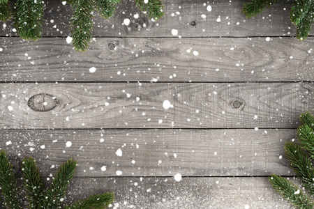 Christmas background - fir branch and snowflake on rustic wood table. Creative top view composition with border and copy space design.