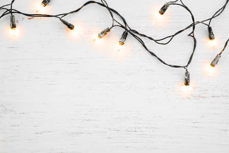 Christmas lights bulb decoration on white wood. Merry Christmas and New Year holiday background. top view Stockfoto