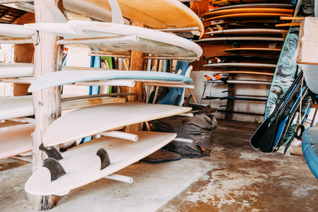 Set of different colorful surf boards in a stack available for rent on the beach.