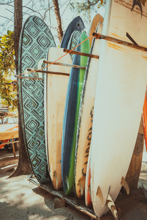 Set of different colorful surf boards in a stack available for rent on the beach. Vertical surfboards, vintage color tone effect.
