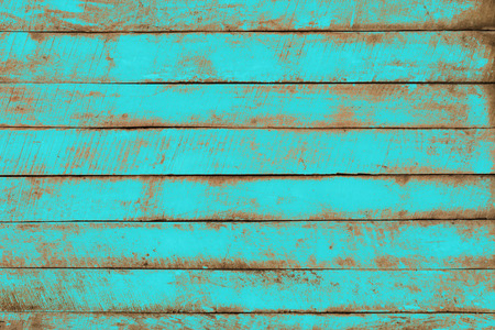 Old weathered wooden plank painted in turquoise blue color. Vintage beach wood background.