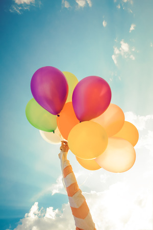 Girl hand holding multicolor balloons done with a retro instragram filter effect, concept of happy birth day in summer and wedding honeymoon party, Vintage color tone style