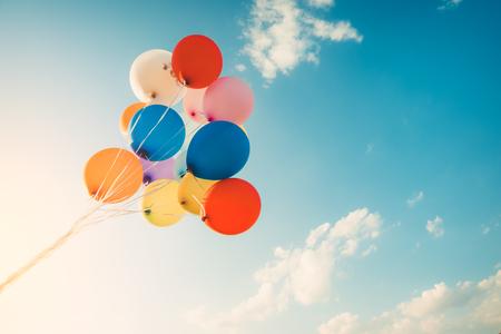 レトロなフィルター効果で行われるカラフルな風船。夏と結婚式で幸せな出産の日のコンセプト、背景のためのハネムーンパーティーの使用。ヴィンテージカラートーンスタイル