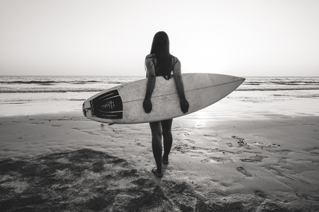 Nostalgia and remembrance photo of surfer woman in bikini go to surfing. beautiful woman with surfboard on beach. black and white color tone. Stock Photo