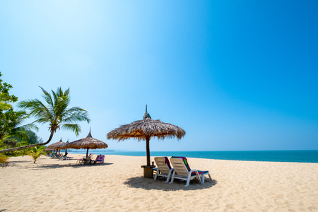 Beach chairs, umbrella and palms on sandy beach near sea. island in Phuket, Thailand. Travel inspirational, Summer holiday and vacation concept for tourism relaxing.