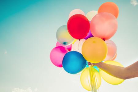 Mano de niña sosteniendo globos multicolores hechos con un efecto de filtro retro, concepto de feliz día de nacimiento en verano y fiesta de luna de miel de boda, estilo de tono de color vintage
