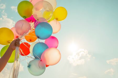 Hand hält mehrfarbige Ballons mit einem Retro-Vintage-Fotofiltereffekt.