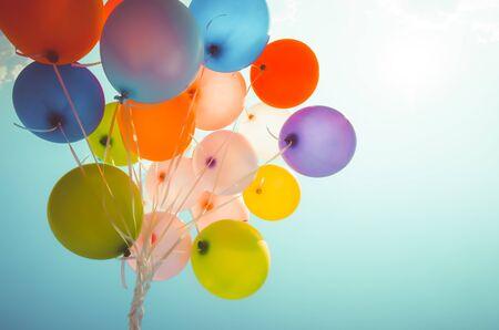 Bunte Luftballons mit einem Retro-Fotofiltereffekt. Konzept des alles Gute zum Geburtstag im Sommer und Hochzeit, Flitterwochen-Partygebrauch für den Hintergrund. Vintage-Farbton-Stil