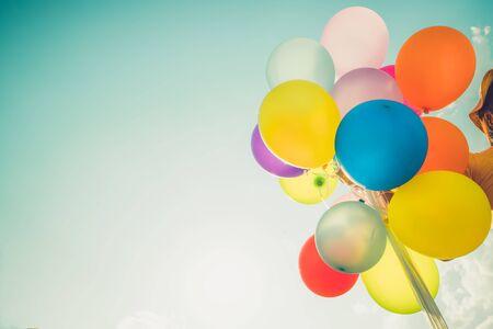 Mädchenhand, die mehrfarbige Ballons mit einem Retro-Fotofiltereffekt hält, Konzept von Happy Birthday im Sommer und Hochzeitsflitterwochen-Party, Vintage-Farbton-Stil