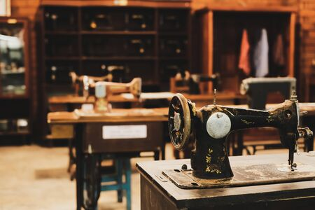 Old sewing machine in workplace of garment factory. retro technology. vintage color tone. Archivio Fotografico