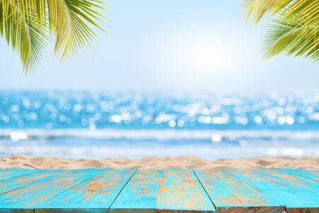 Top of wood table with seascape and palm leaves, blur bokeh light of calm sea and sky at tropical beach Reklamní fotografie