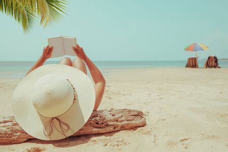 Leisure in summer - Young woman in straw hat lying sunbathe on a tropical beach, relax with book. Memories of summer vacation concept. retro color tone.