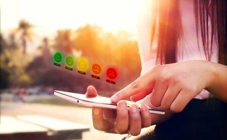 Kundenservice-Erfahrung und Umfragekonzept zur Geschäftszufriedenheit. Frauenhand mit Smartphone mit Symbolgesichtssymbol, um Zufriedenheit zu wählen.
