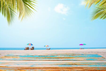 Top of wood table with seascape, palm leaf, calm sea and sky at tropical beach background. Empty ready for your product display montage.  summer vacation background concept.