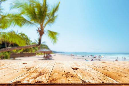 Top of wood table with seascape, palm tree, calm sea and sky at tropical beach background. Empty ready for your product display montage.  summer vacation background concept.