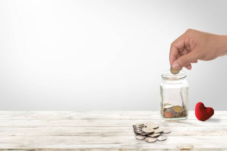 Hand of male insert coins in piggy bank saving money for health investment. Insurance policy to accumulate assets and Investment health and insurance fund concept.