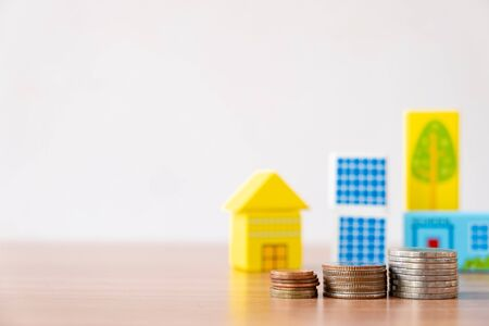 Property investment and house mortgage financial concept. Money coin stack with wooden house and real estate