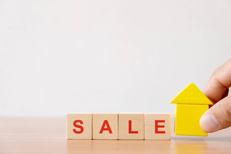 Property investment and house mortgage financial concept. Hands holding wooden house and wood cube block with SALE word.