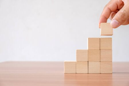 Business concept of ladder career path and growth success process. Hands of men arranging wood cube block stacking for top staircase shape on wooden table. Stockfoto