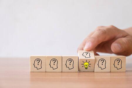 Concetto di business di idea creativa e innovazione. Capovolgere a mano il blocco cubo di legno con l'icona della lampadina (nuova idea) e il simbolo della testa umana non hanno idea. Archivio Fotografico