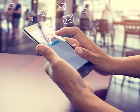 Hand des Mannes, der Mobiltelefon verwendet, um E-Mail-Nachricht mit E-Mail-Symbol und Umschlagsymbol zu senden. E-Mail-Marketing-Konzept