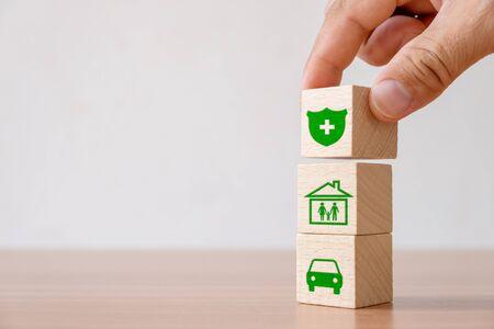 Assicurazione e concetto di investimento di salute, vita, incidenti e viaggi. Blocco di legno raccolto a mano con segno di assicurazione e simbolo di casa, famiglia, auto Archivio Fotografico