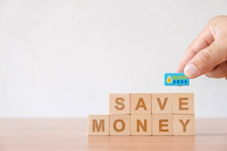 Concept of finance business investment, growth saving money. Hand picked with currency symbol and wooden cube with word save money. Reklamní fotografie
