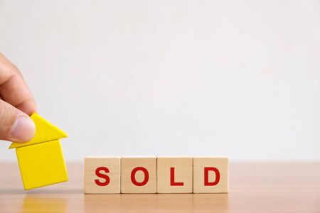 Property investment and house mortgage financial concept. Hands holding wooden house and wood cube block with SOLD word.
