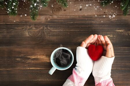 Above view of woman hand holding red heart with hot cup of coffee on wood table. Christmas holiday and winter season Imagens