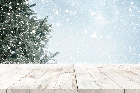 Top of empty wood table with fir tree and snowfall  backdrop. ready for your product display or montage. Concept of background in Christmas and winter holidays. 免版税图像