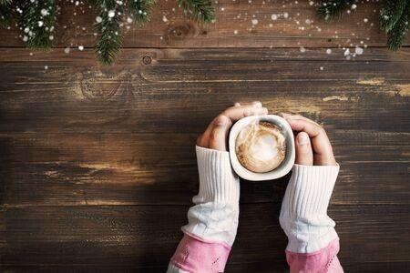 Vista anterior de la mano femenina sosteniendo una taza de café caliente en la mesa de madera.