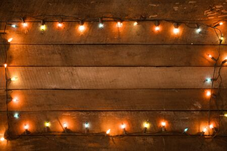Kerstverlichting lamp decoratie op oude houten plank, frame boordmotief. Vrolijke Kerstmis en Nieuwjaar vakantie achtergrond. vintage kleurtoon. Stockfoto