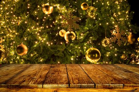 Beautiful Christmas tree backdrop and lights with top of empty wood table. ready for your product display or montage. Concept of background in Christmas and New year holidays.