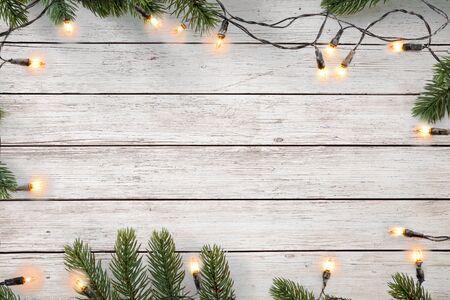 Weihnachtsbeleuchtung Glühbirne und Kiefernblätter Dekoration auf weißem Holzbrett, Rahmenrahmendesign. Feiertagshintergrund der frohen Weihnachten und des neuen Jahres. Ansicht von oben. Standard-Bild