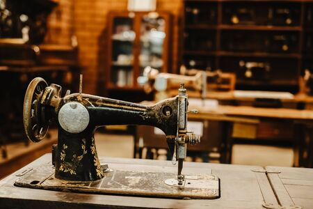 vintage sewing machine in workplace of garment factory. retro technology. vintage color tone. Stock Photo