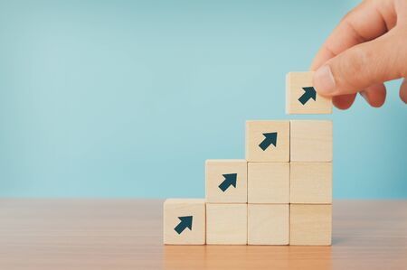 Business concept of ladder career path and growth success process. Hands of men arranging wood cube block stacking as step stair with arrow up.