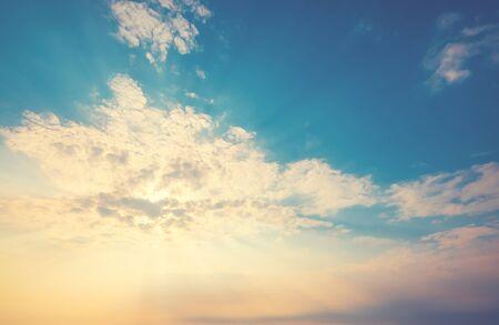 gelbes Sonnenlicht der Sonne durch die Wolken über dem blauen Himmel. Sonnenschein am Morgen. Vintage-Farbeffekt Standard-Bild