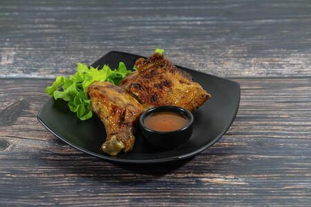 Grilled chicken on wooden board with sauce