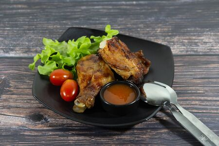 Grilled chicken on wooden board with sauce and tomato