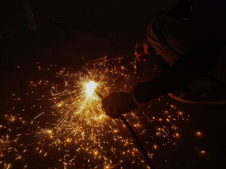 A man mechanic was using a gas nozzle to cut the wire rope until a fire broke on the ground. Reklamní fotografie