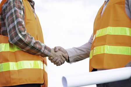 Two Asian engineers wearing reflective jackets and standing building plan besides the construction project and handshake, agree on an employment contract or join a job or consult a job.