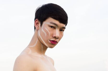 One Asian gay handsome man not wearing a shirt, he writes on the face and wears pink lipstick. Copy space