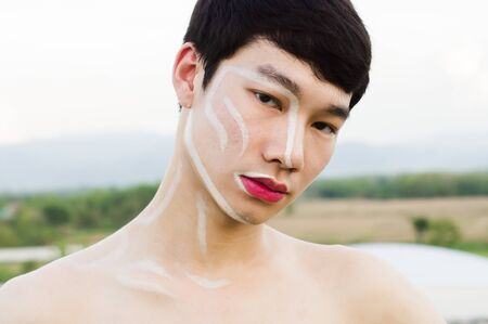One Asian handsome man not wearing a shirt, he writes on the face and wears pink lipstick. Copy space