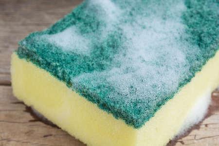 dishwashing: Closeup dishwashing sponge with foam on wooden background