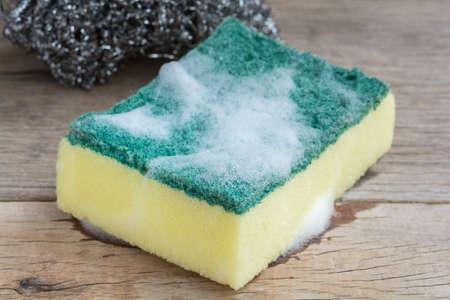 lavar platos: Lavar platos esponja con espuma en el fondo de madera Foto de archivo