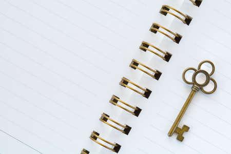 diagonal diary education: A gold metal key on white paper