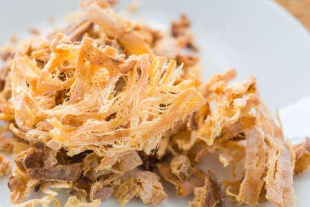 seasoned: Shredded seasoned cuttlefish on a white dish