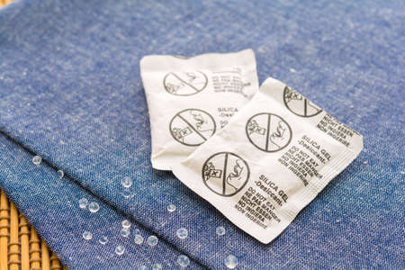 Desiccant or silica gel in paper sachet on blue fabric background