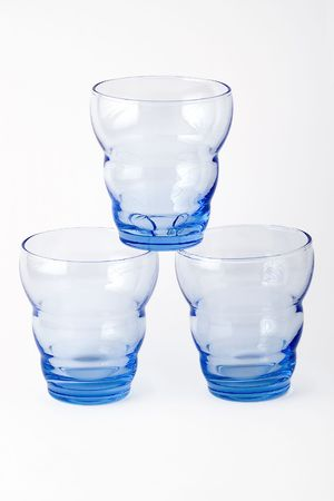 eachother: 3 blue glasses standing on top of eachother, with white background Stock Photo
